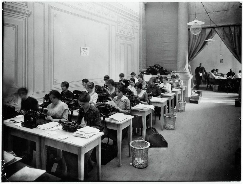 Suisse. Guerre 1914-1918. Genève, Musée Rath, Agence internationale des prisonniers de guerre. Service dactylographique. ©CICR. V-P-HIST-00578-35. — Au fond à droite, de face : Romain Rolland