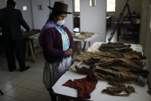 A relative of a missing person examines the items of clothing of four missing persons in Peru, in an effort to identify her relative