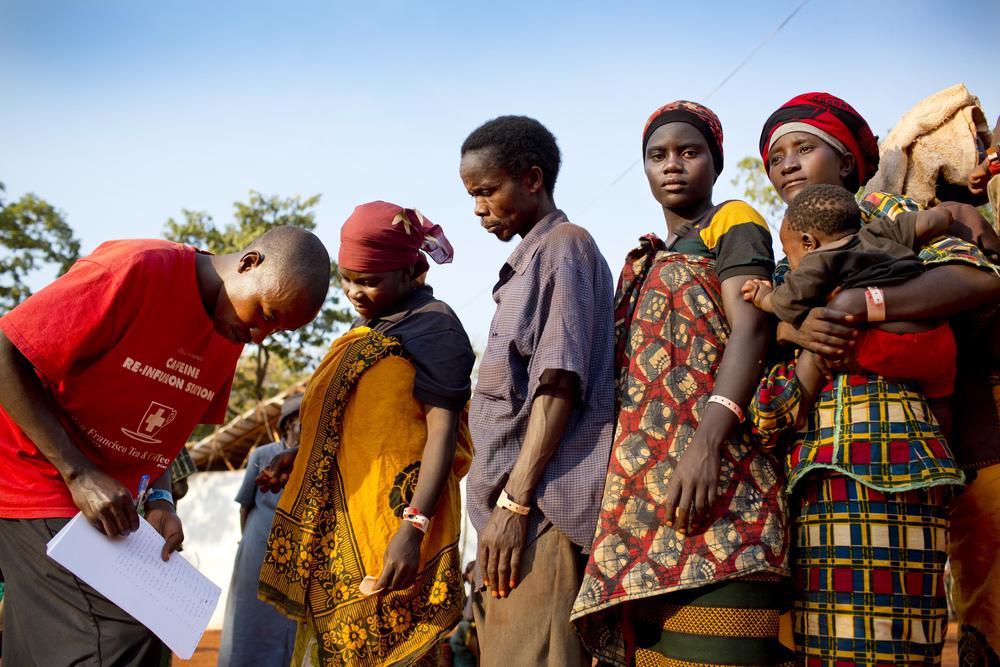 מחנה הפליטים ניאגוּרוּסוּ בטנזניה. פליטים שזה עתה הגיעו מבורונדי נרשמים אצל חבר באגודת הצלב האדום של טנזניה.