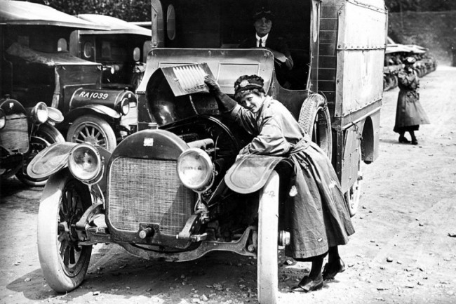 France, Étaples, 1914-1918 war. An ambulance driver examines her vehicle's engine before departure. © Imperial War Museum London / hist-00215-55