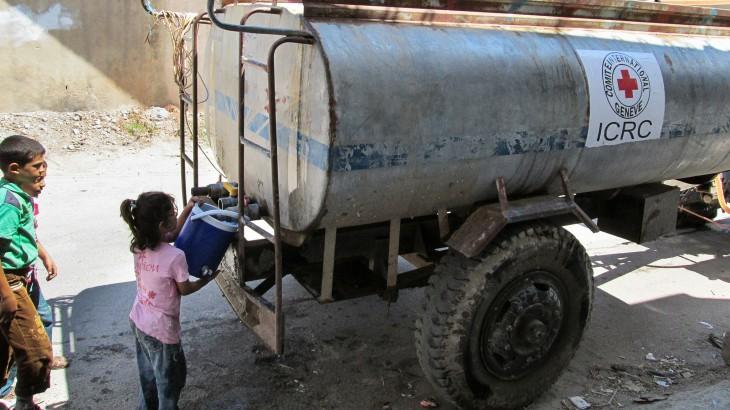 חומס, סוריה. ילדה עקורה ממלאת מים ממכלית מים של ה-ICRC. CC NY-NC-ND/ICRC/SY-E-00308