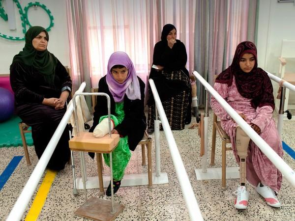 ארביל, עיראק. מסריה סחר, בת 13 (משמאל), ואחותה סעדה, בת 16, איבדו שתיהן את רגל ימין שלהן ממוקשים נגד אדם. בעזרת אמן (היושבת מאחוריהן), הן לומדות ללכת על הרגליים התותבות החדשות שלהן במרכז לשיקום פיזי של ה-ICRC בארביל. Getty Images/ICRC/Marco Di Lauro