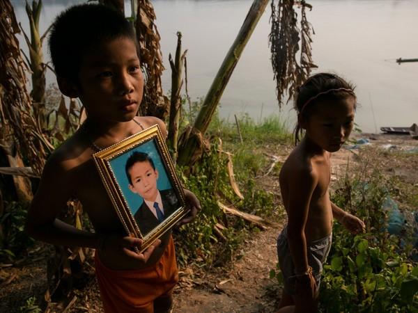 האנגסינג, מחוז פקסן, לאוס. מֶק, בן 9, מחזיק תמונת דיוקן של סומאק טו, בן 12 – אחד משלושת הבנים שנהרגו מפריט נפל תחמושת שהם סחבו הביתה באופניים. בין 1963 ל-1972, במהלך מלחמת ווייטנאם, הוטלו על לאוס יותר מ-270 מיליון פצצונות (הפצצות הקטנות שבתוך פצצות המצרר). Getty Images/ICRC/Paula Bronstein