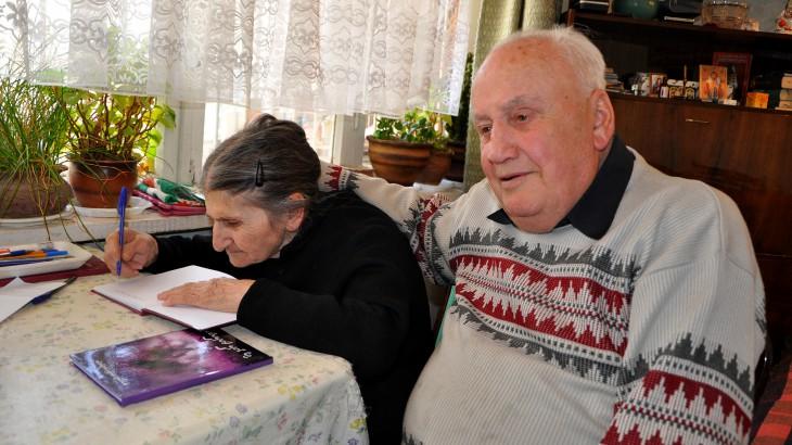 גאורגיה. זוּזוּנה אוֹקרוּאָשווילי, שבנה נעדר במשך 24 שנים, יושבת לצד בעלה וָלֶרְיאן וחותמת על עותק של ספר שירה שכתבה כדי להביע את רגשותיה. CC BY-NC-ND / ICRC