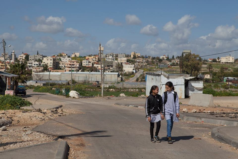 Azzoun Atmehh, West Bank. Rudayna and her friend walk back from school. With the checkpoint dismantled, their walk to and from school has become much shorter and more fun. © ICRC / Andrea & Magda