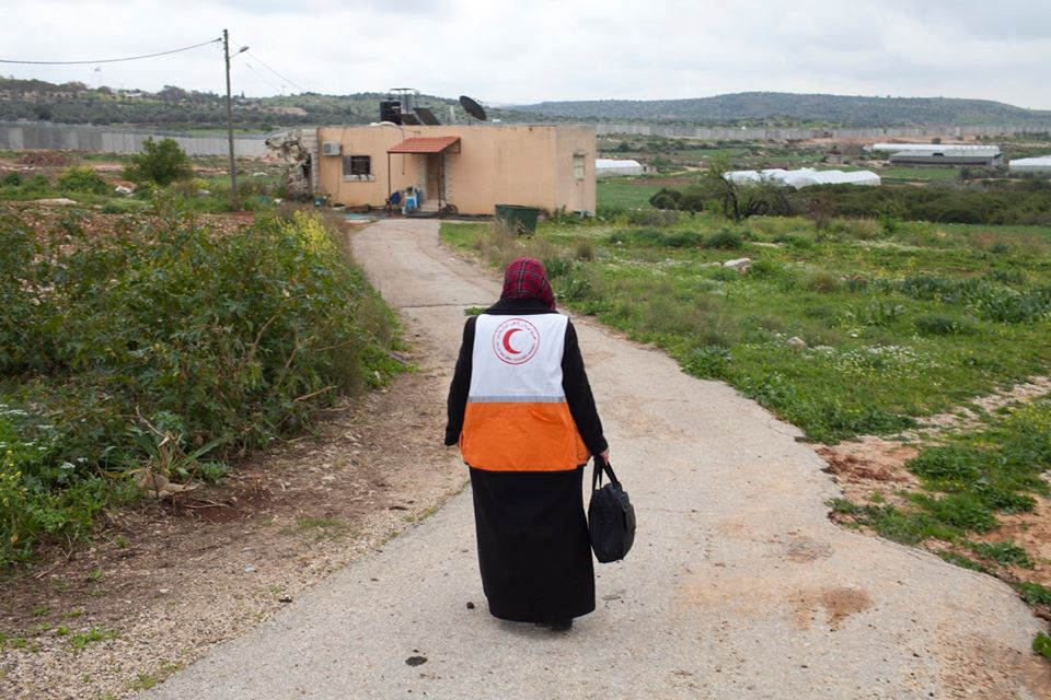 Fawzeyeh, a nurse with the PRCS, visits a family in the ex-enclave. In the past, medical intervention was subject to prior coordination with the Israeli army; now, Fawzeyeh can visit families directly as the need arises. © ICRC / Andrea & Magda