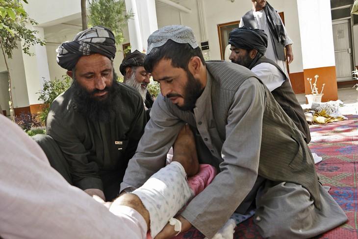 זמאריאלאי (מימין) מתרגל קיבוע בסד של רגל שבורה תוך שימוש בחומרים זמינים לפני העברת פצוע לבית חולים. CC BY-NC-ND / ICRC / Shamshad Omar
