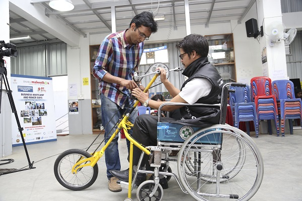 A device that turns a wheelchair into a tricycle suited to difficult terrain