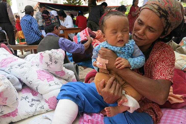 Pemi Tamang dari Chhumdi Village di Sindhupalchok, yang mengalami luka parah pada kakinya  masih bisa menghibur bayinya yang menangis. CC BY-NC-ND / ICRC / Devendra Dhungana