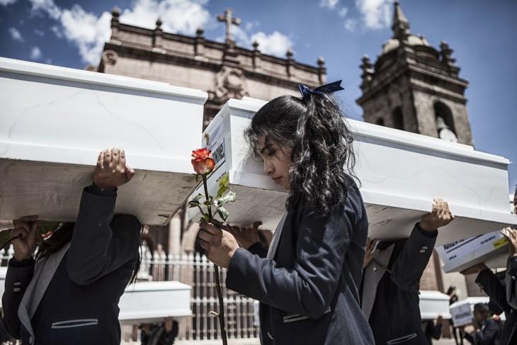 Anggota keluarga dan para relawan membawa peti mati di sepanjang jalan Ayacucho. [Nadia Shira Cohen / ICRC]