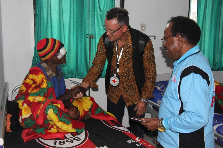 Christoph Sutter, Kepala Delegasi Regional ICRC Indonesia & TImor Leste, dan Ketua PMI Provinsi Papua, Johanis Safkaur, bercengkama dengan salah satu pasien setelah operasi katarak pada hari sebelumnya. ©Mia Pitria/ICRC
