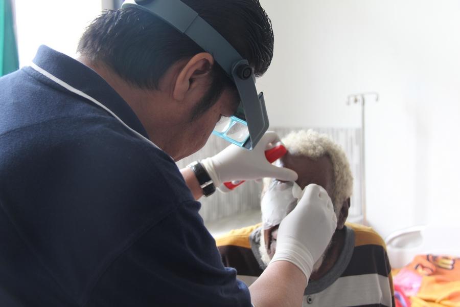 Dr. Decky, melakukan pemeriksaan mata kepada salah satu pasien sehari setelah operasi katarak. ©Mia Pitria/ICRC