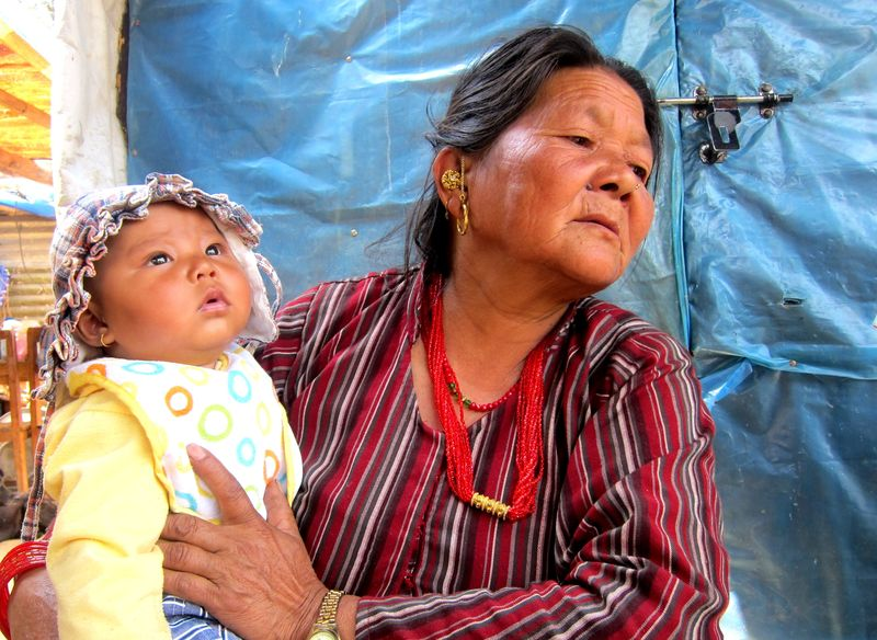 With her grandson in the arms, Kanchhi Tamang looks over an empty patch of land where her house once existed. ©ICRC, Tanvi