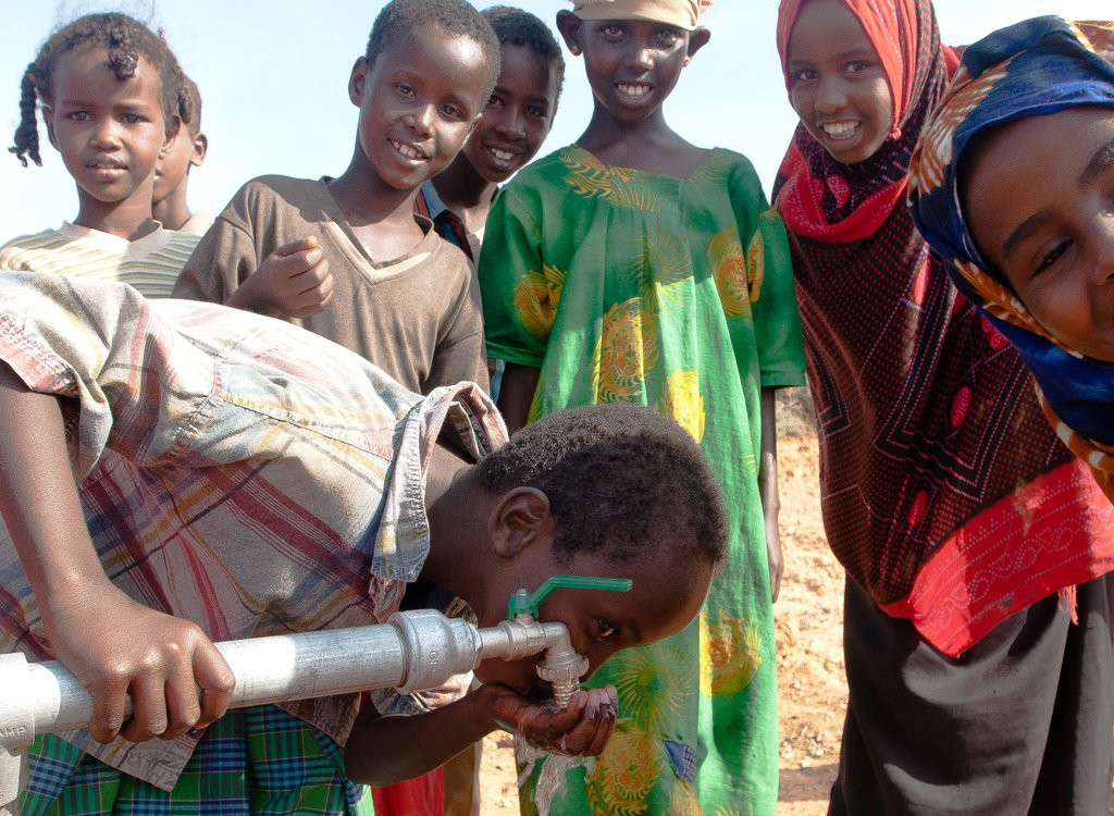 Cheerful children in Somalia take turns drinking from a freshly installed tap. ©ICRC/Pedram Yazdi