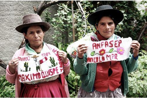 สองแม่ลูกแสดงผืนผ้าที่ถักทอเสร็จแล้ว