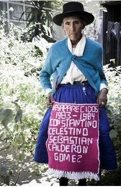 หญิงชาวเปรูแสดงผืนผ้าที่ถักทอเสร็จแล้ว