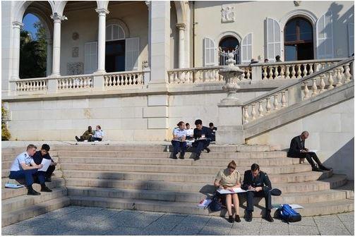 นักเรียนนายร้อยที่เข้าร่วมการแข่งขันจับกลุ่มหารือด้านนอกตัวอาคารสถาบัน