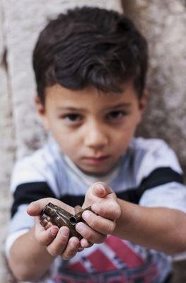 เด็กชายถือปลอกกระสุนปืนที่เก็บได้ อเลปโป ซีเรีย ปี 2013