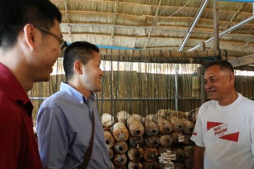 ไดซากุ โอกะ และพู ซกวิศาล ผู้แทนของ ICRC ผู้ริเริ่มและรับผิดชอบโครงการเศรษฐกิจครัวเรือนขณะพูดคุยกับครอบครัวของหนึ่งในผู้สมัครเข้าโครงการที่ทำฟาร์มเห็ด